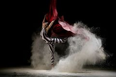 Beautiful girl on cloth in dust cloud shot. Beautiful girl wearing striped body dancing on cloth in white dust cloud profile shot in the dark stock images