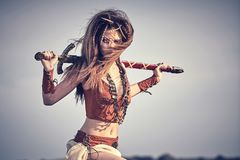A beautiful girl in clothes and ornaments of Vikings or Amazons. In, with a sword against the sky. Closeup portrait Stock Images