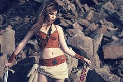 A beautiful girl in clothes and ornaments of Vikings or Amazons. In, with a sword on the background of stones. Closeup portrait Royalty Free Stock Photo