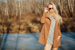 Beautiful girl in a coat posing against the background of a spring nature stock photos
