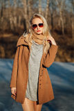 Beautiful girl in a coat posing against the background of a spring nature Royalty Free Stock Image