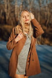 Beautiful girl in a coat posing against the background of a spring nature Royalty Free Stock Photos