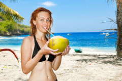 Beautiful girl with coconut on background of ocean Royalty Free Stock Photography