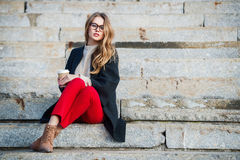 Beautiful girl with coffee cup sitting on outdoors stairs wearing red pants and glasses. Royalty Free Stock Photos
