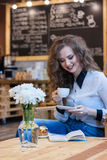 Beautiful girl with coffee reading a book Royalty Free Stock Photo