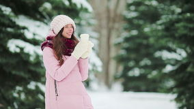 Beautiful girl with coffee to go outdoors on beautiful winter snow day stock video