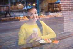 Beautiful girl with coffee viewed through the window Royalty Free Stock Photo