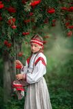 A beautiful girl collects bunches of mountain ash in the hem of her dress