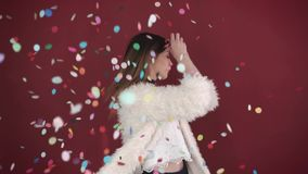 Beautiful girl among color confetti, slow motion. woman dancing among confetti over red background. stock footage