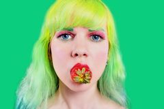 Beautiful girl with color hair holds strawberry with lips on green background Stock Photo