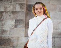 Beautiful girl with colored dreadlocks summer sunny day in a white jacket fun posing near the wall Stock Photo