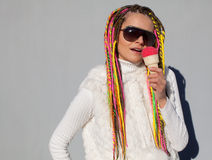 Beautiful girl with colored dreadlocks summer sunny day in a white jacket with sunglasses eating pink ice cream nex to grey wall Stock Photos
