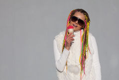 Beautiful girl with colored dreadlocks summer sunny day in a white jacket with sunglasses eating pink ice cream nex to grey wall. Beautiful girl with colored Stock Image