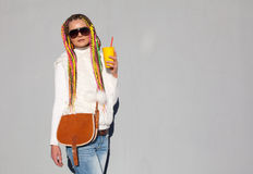 Beautiful girl with colored dreadlocks summer sunny day in a white jacket with sunglasses holding a yellow glass with a vintage br Royalty Free Stock Photo