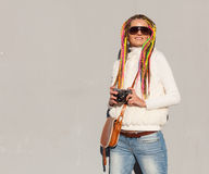Beautiful girl with colored dreadlocks summer sunny day in a white jacket with sunglasses with a vintage brown bag over her should Royalty Free Stock Photography