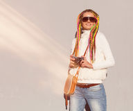 Beautiful girl with colored dreadlocks summer sunny day in a white jacket with sunglasses with a vintage brown bag over her should Stock Photo