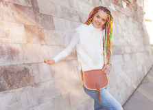 Beautiful girl with colored dreadlocks summer sunny day in a white jacket with a vintage brown bag over her shoulder fun posing ne Royalty Free Stock Photo