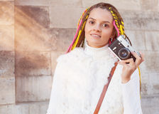 Beautiful girl with colored dreadlocks summer sunny day in a white jacket with a vintage brown bag over her shoulder holding in he Royalty Free Stock Image