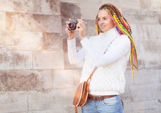Beautiful girl with colored dreadlocks summer sunny day in a white jacket with a vintage brown bag over her shoulder vintage camer Royalty Free Stock Image