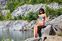 Beautiful  girl in colorful bikini sits on a rock near the mount Stock Image