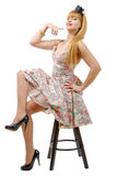 Beautiful girl in colorful dress sitting on a stool Stock Images