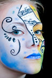 Beautiful girl with colorful face paint. Young woman with blue, yellow and black face paint with a very intense gaze Royalty Free Stock Image