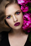 Beautiful girl with colorful make-up, flowers, retro hairstyle. beauty face. Royalty Free Stock Photography