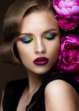 Beautiful girl with colorful make-up, flowers, retro hairstyle. beauty face. Royalty Free Stock Photos
