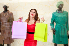 Beautiful girl with colorful packages admired in the store Stock Photos