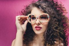 Beautiful girl with colourful manicure in confectionery dressing glasses royalty free stock photos