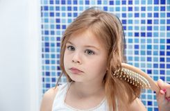Beautiful girl is combing her hair in the bathroom. Girl got h stock photos