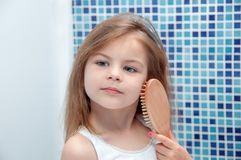 A beautiful girl is combing her hair in the bathroom. Stock Images