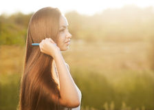 Beautiful girl combs her hair Stock Photos