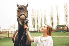 Beautiful girl communicates with a horse in the park Royalty Free Stock Photo