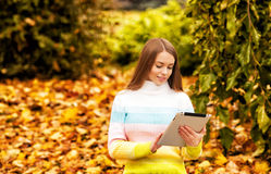 Beautiful girl with computer tablet at autumn Royalty Free Stock Images
