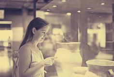 Beautiful girl considers exhibits in museum Stock Images