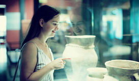 Beautiful girl considers exhibits in museum Stock Photography