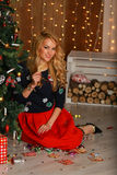 Beautiful girl with cookies hands sits near a Christmas tree. Royalty Free Stock Photos