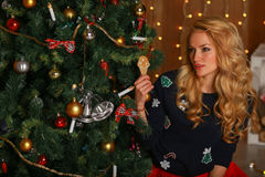 Beautiful girl with cookies hands sits near a Christmas tree. Royalty Free Stock Images