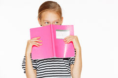 Beautiful girl with copybook. Beautiful little girl in blue dress with copybook. Isolated on white Royalty Free Stock Photo