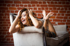 Beautiful girl on the couch. Girl lying on the coach. retro style, dark interior. happy girl on the couch Royalty Free Stock Images