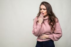 Beautiful young girl coughing isolated on gray background. Beautiful girl coughing isolated on a gray background stock images