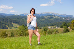 Beautiful girl in country style clothes. Standing at grass meadow Stock Photo