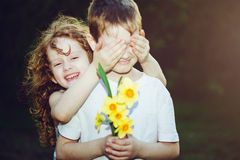 Beautiful girl covering her boyfriends eyes and boy with bouque Royalty Free Stock Photos