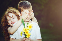 Beautiful girl covering her boyfriends eyes and boy with bouque Stock Photos