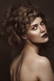 Beautiful girl with creative hairstyle art, perfect skin and dark makeup. The beauty of the face. Stock Photo