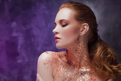 Beautiful girl with creative image with gold foil on the neck. Blue and purple toning royalty free stock photography