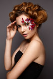 Beautiful girl with creative make-up with floral appliques. The model in the style of romantic with flower petals around her eyes. The photo was made in a Stock Photo