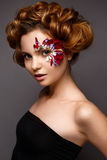 Beautiful girl with creative make-up with floral appliques. The model in the style of romantic with flower petals around her eyes. The photo was made in a Royalty Free Stock Photos