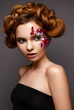 Beautiful girl with creative make-up with floral appliques. The model in the style of romantic with flower petals around her eyes. Stock Images